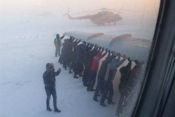 Пассажирам пришлось толкать самолет, примерзший к взлетной полосе