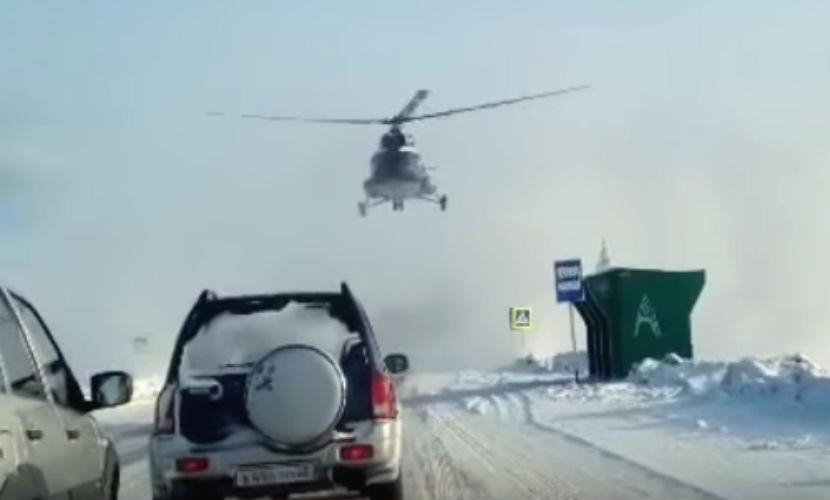 Удивленные сибирские автомобилисты сняли видео приземления на трассу вертолета