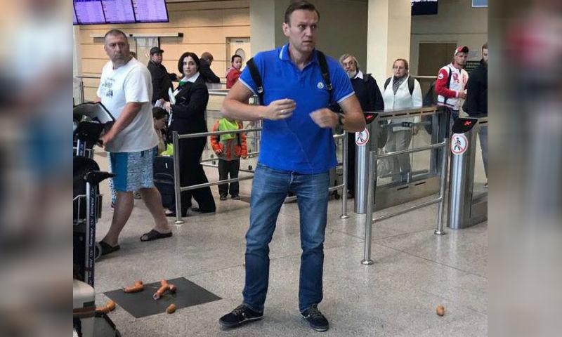 Навальному надели венок из сарделек на шею в аэропорту Домодедово