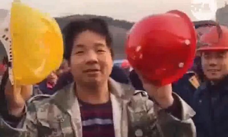 Китайский рабочий показывает разницу между касками для рабочих и руководителей