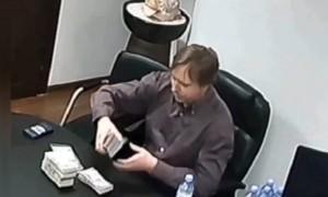 Масляков-младший укладывает в портфель пачки долларов