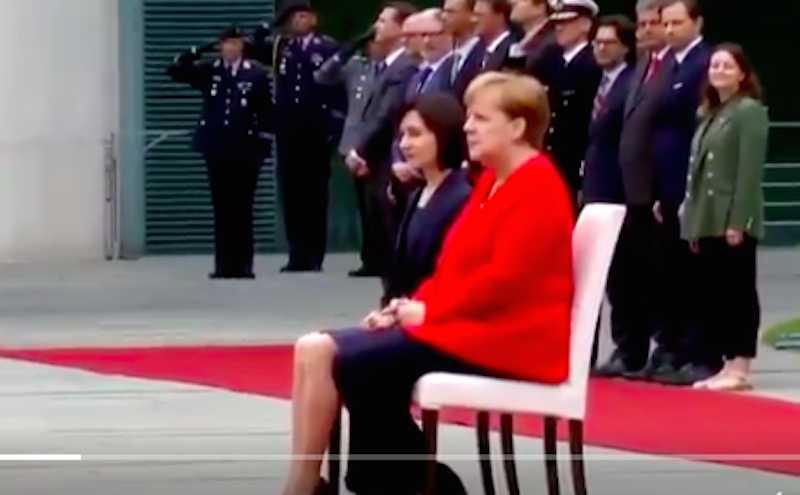 Меркель вынуждена сидя слушать гимны
