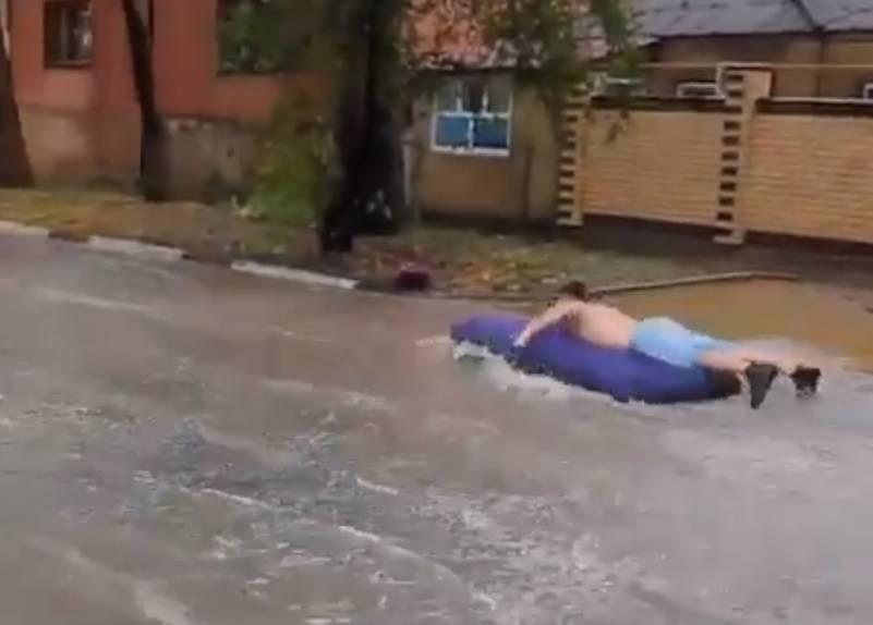 В Анапе мужчина устроил заплыв на матрасе по затопленной улице